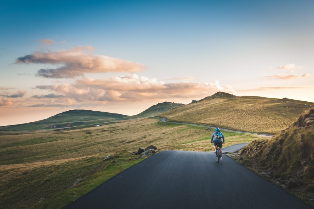 person cycling on road distance with mountain during daytime